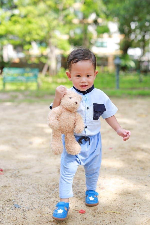 走外面与藏品玩具熊的愉快的小孩男孩在室外的公园 免版税库存图片