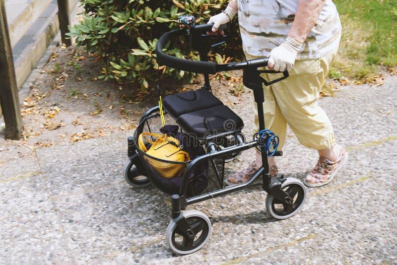 走外面与rollator或被转动的步行者的年长妇女 免版税库存图片