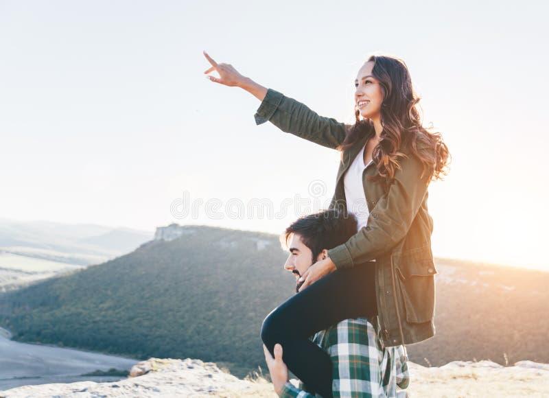 走外面在美好的日落的年轻美好的夫妇 在她的男朋友的肩膀的美女sittiong 免版税库存图片
