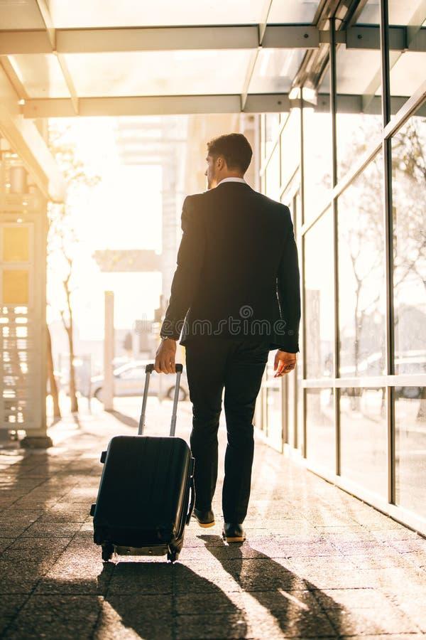 走带着在机场大厦之外的手提箱的年轻商人 免版税库存照片