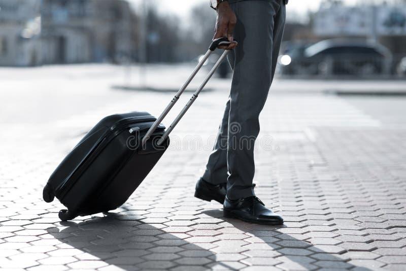走带着手提箱的商人户外,抵达机场 图库摄影