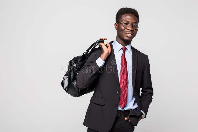 走带着他的包的友好的黑商人微笑和愉快在灰色背景 免版税库存照片
