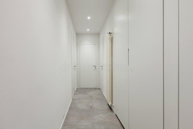 走廊与瓦片的所有白色在地板上 库存图片