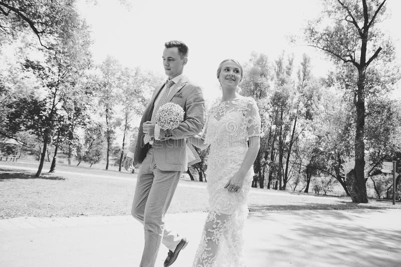 走开在夏天公园的新娘和新郎户外 免版税库存图片