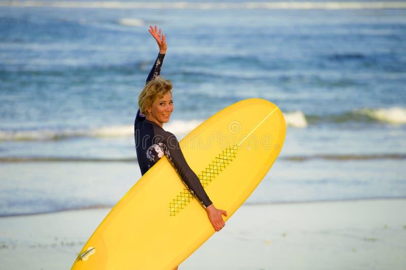 走往海的年轻美丽和愉快的冲浪者女孩运载黄色水橇板准备好冲浪的微笑的快乐的enjoyi 库存照片