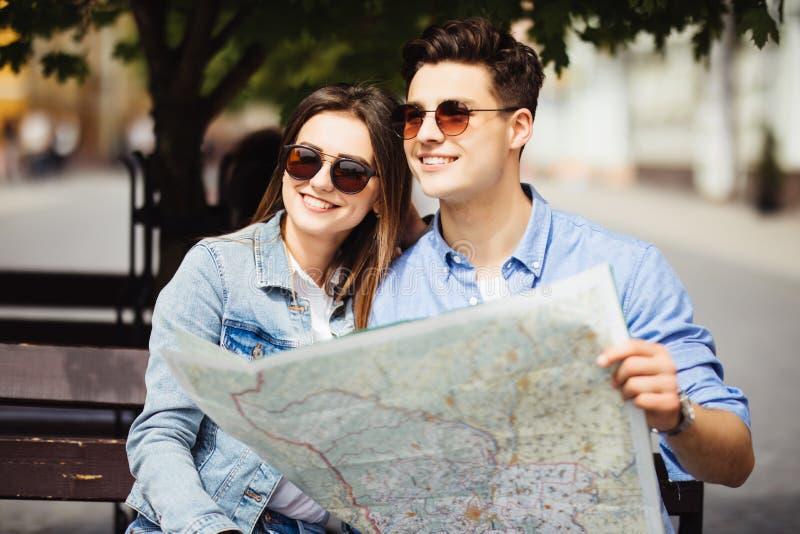 走愉快的夫妇户外观光和拿着一张地图在新的城市 汽车城市概念都伯林映射小的旅行 图库摄影