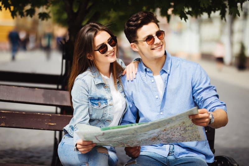 走愉快的夫妇户外观光和拿着一张地图在新的城市 汽车城市概念都伯林映射小的旅行 库存照片