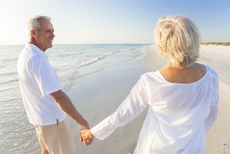 走愉快的高级的夫妇拿着现有量热带海滩 库存图片