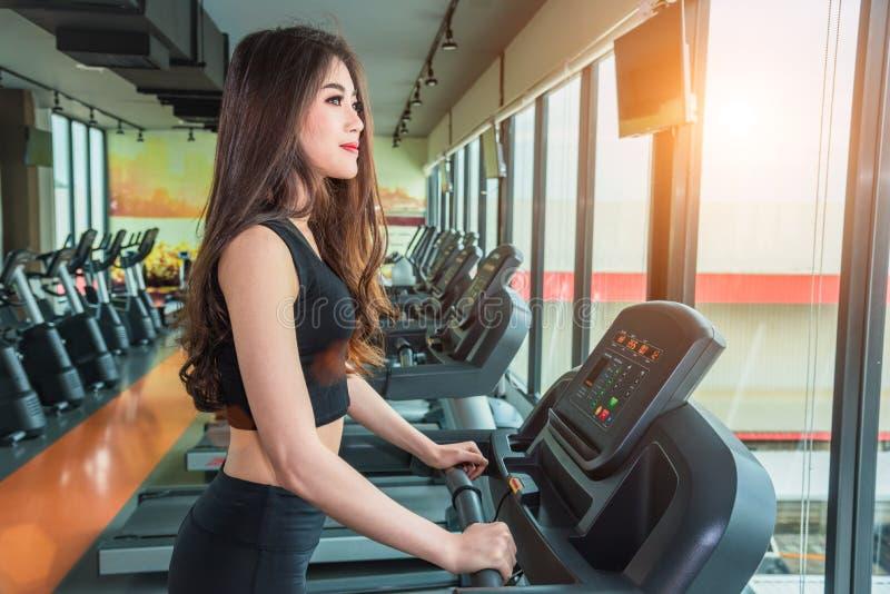 走或跑在健身锻炼健身房的踏车设备的亚裔体育妇女 体育和秀丽概念 锻炼和力量 免版税库存图片