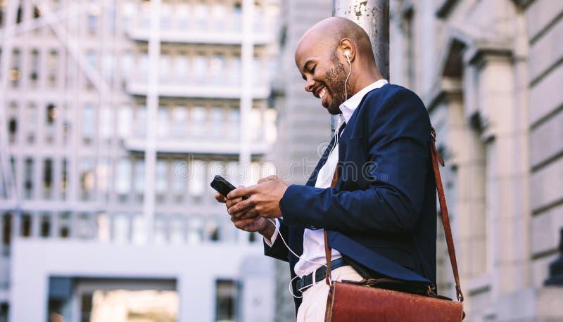 走户外与手机的非洲商人 库存图片