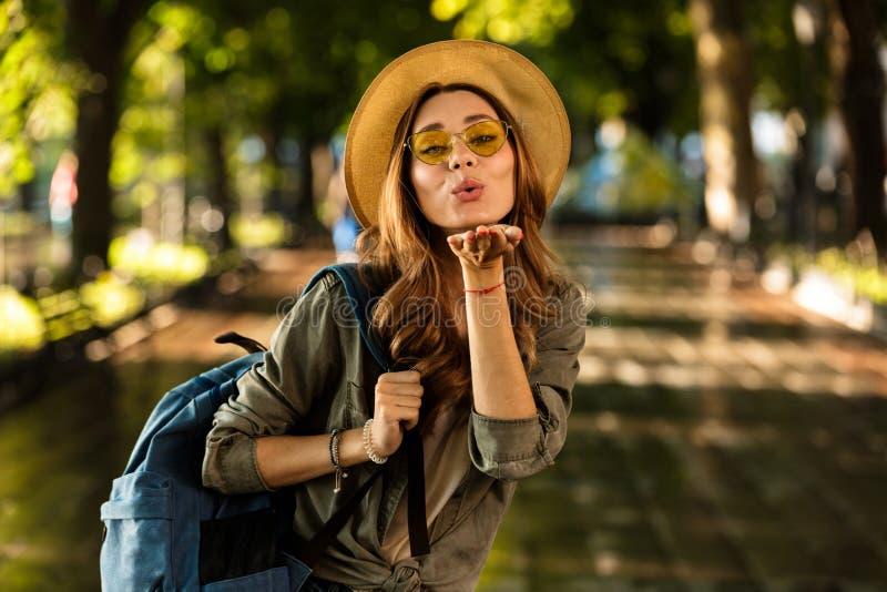 走户外与背包吹的亲吻的美丽的年轻愉快的妇女 库存图片