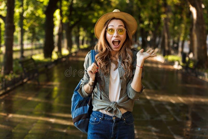 走户外与背包的震惊美丽的年轻愉快的妇女 免版税库存照片