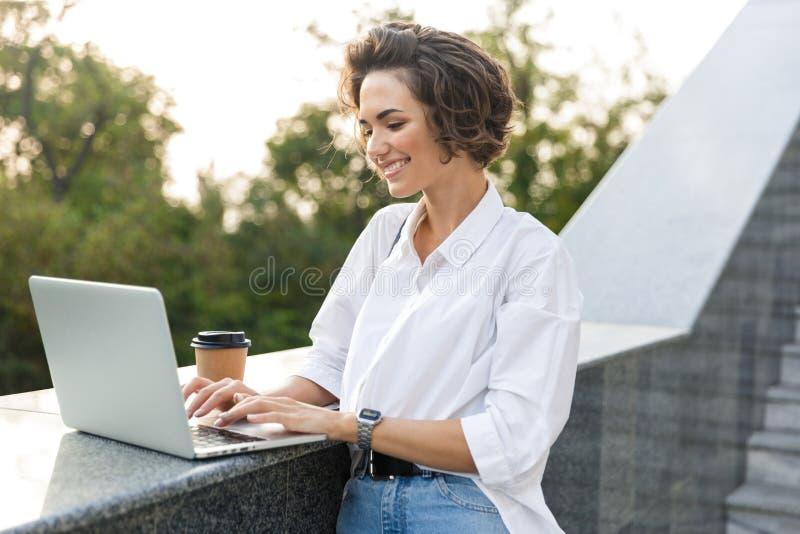 走户外使用手提电脑的逗人喜爱的美女拿着咖啡 免版税库存图片
