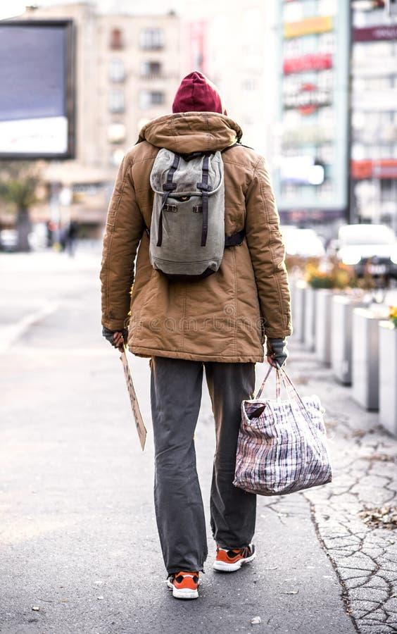 走户外在城市的无家可归的叫化子人一个背面图,拿着袋子 免版税库存图片