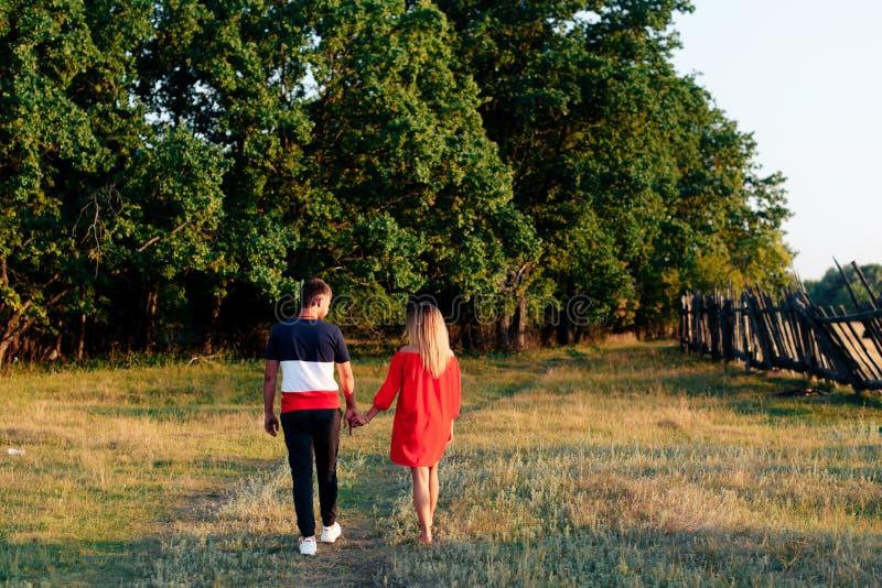 走户外在夏天的年轻美好的被迷恋的夫妇在日落 库存照片
