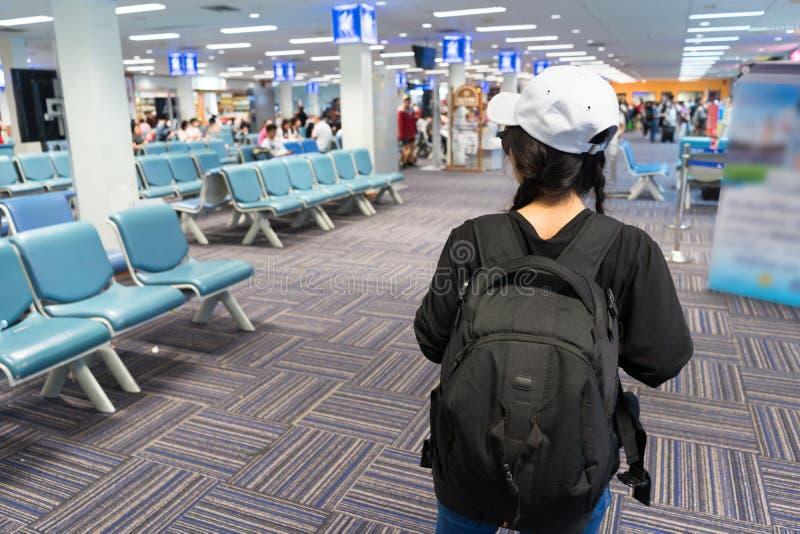 走旅客旅游的女孩正在寻找伙伴在等待的大厅 免版税图库摄影