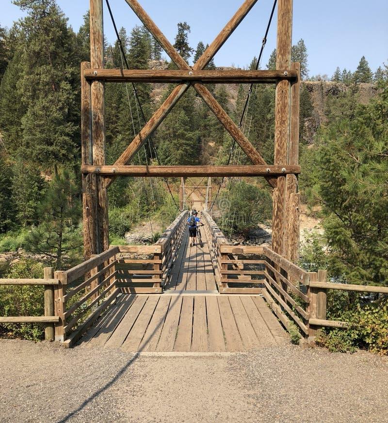 走横跨吊桥的自行车骑士 免版税库存图片