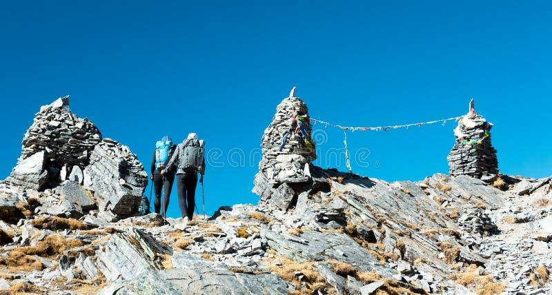走横跨喜马拉雅山山口的两个远足者 免版税库存图片