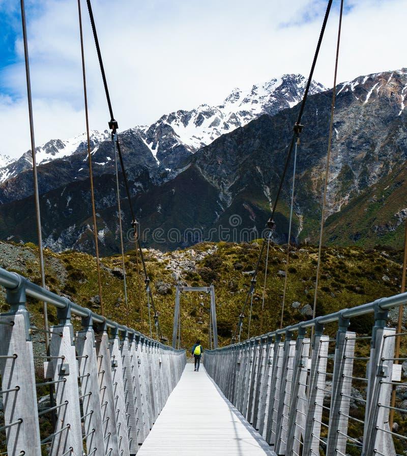 走横跨有山的桥梁的远足者在背景中 免版税库存照片