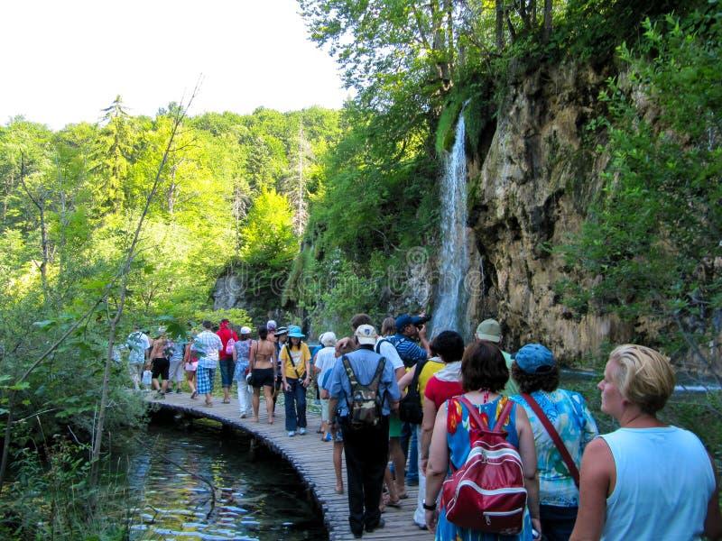 走沿一条狭窄的道路的一个小组游人在疯狂美丽的蓝色湖旁边 Plitvice,克罗地亚2010年7月22日 免版税库存照片