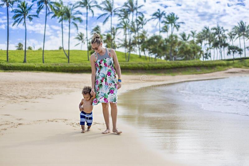 走沿与他的母亲的海滩的逗人喜爱的混合的族种小男孩一个热带海岛假期 图库摄影