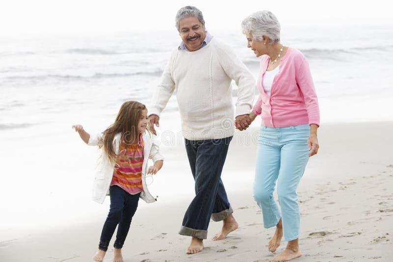 走沿与孙女的海滩的祖父母 免版税图库摄影