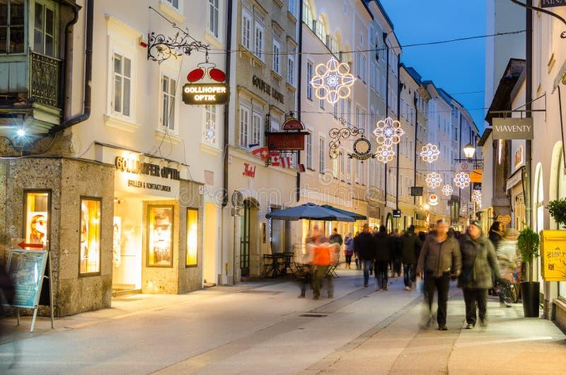 走沿历史的Liznzergasse车道的顾客在萨尔茨堡,奥地利 免版税库存图片