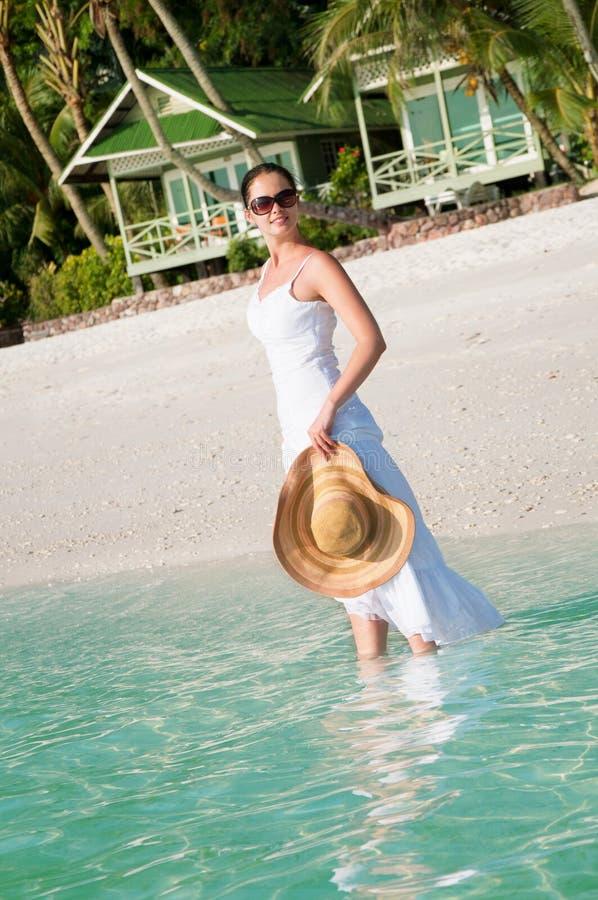 走沿在热带海滩的海边的美丽的妇女 免版税库存图片