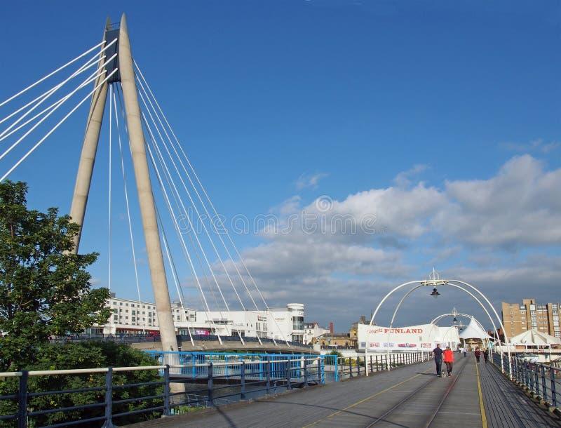 走沿在southport默西赛德郡的码头的人们在与吊桥和大厦的一个明亮的夏日与a 库存照片