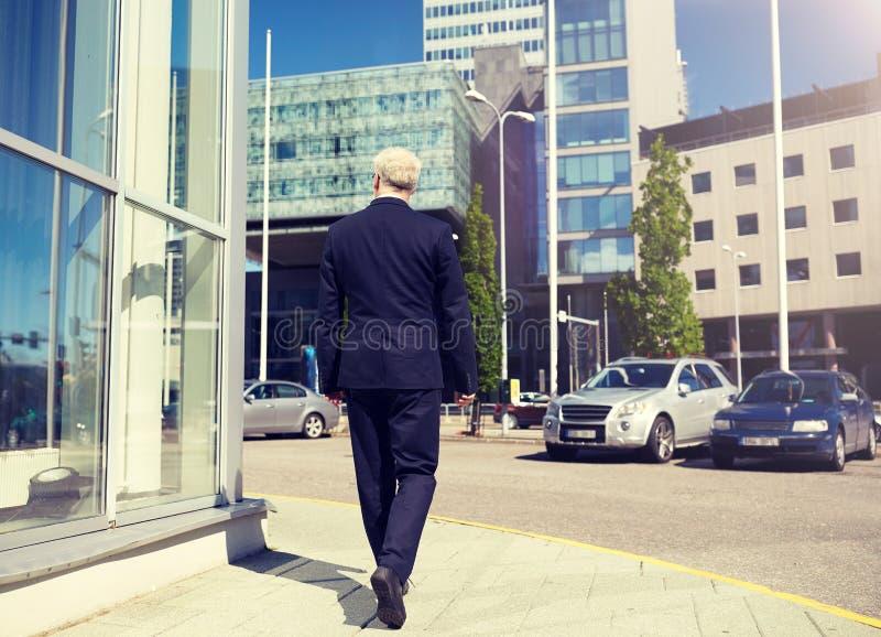 走沿城市街道的资深商人 免版税库存图片