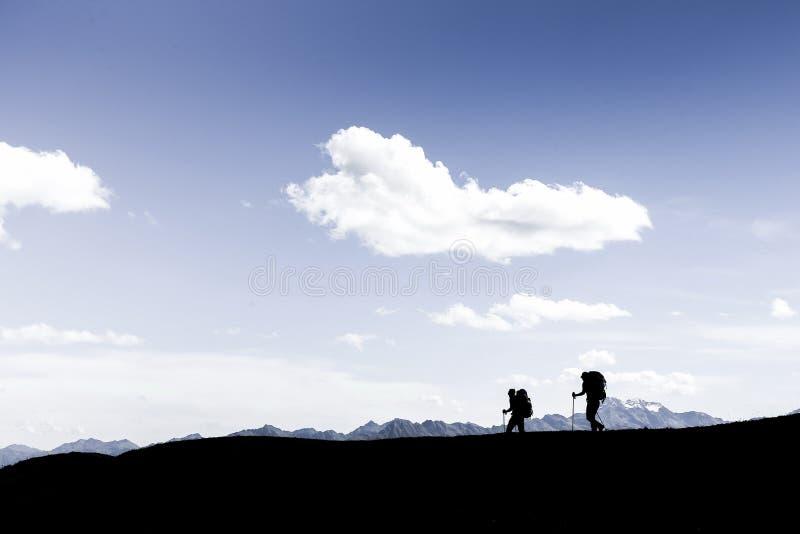 走沿峭壁边缘的两个徒步旅行者剪影  免版税库存照片