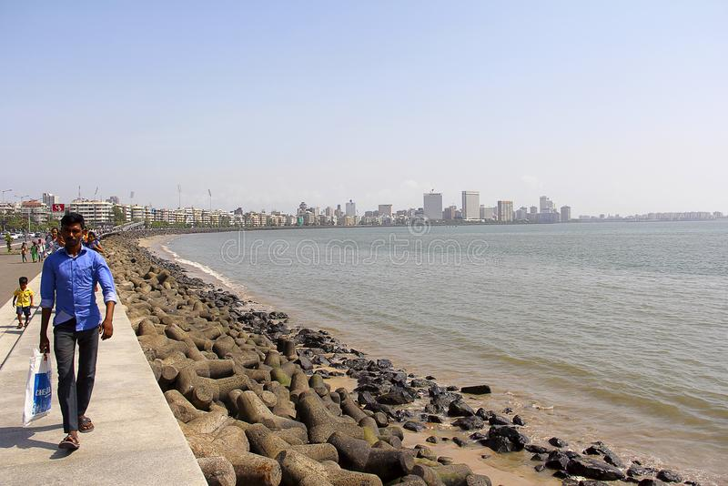 走沿旁边海洋驱动、轻率冒险与海和大厦的人和人们 库存照片