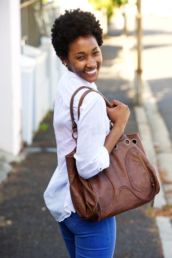 走沿有钱包的一条街道的美丽的少妇 免版税库存照片