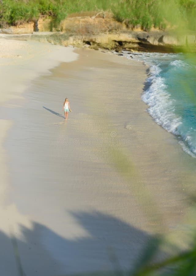 走沿梦想海滩的女孩在lembongan的努沙,巴厘岛,印度尼西亚的日落 免版税库存照片