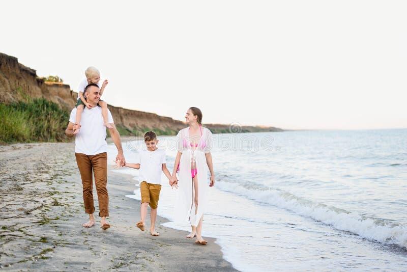 走沿海滨的四口之家 父母和两个儿子 愉快的友好的家庭 图库摄影