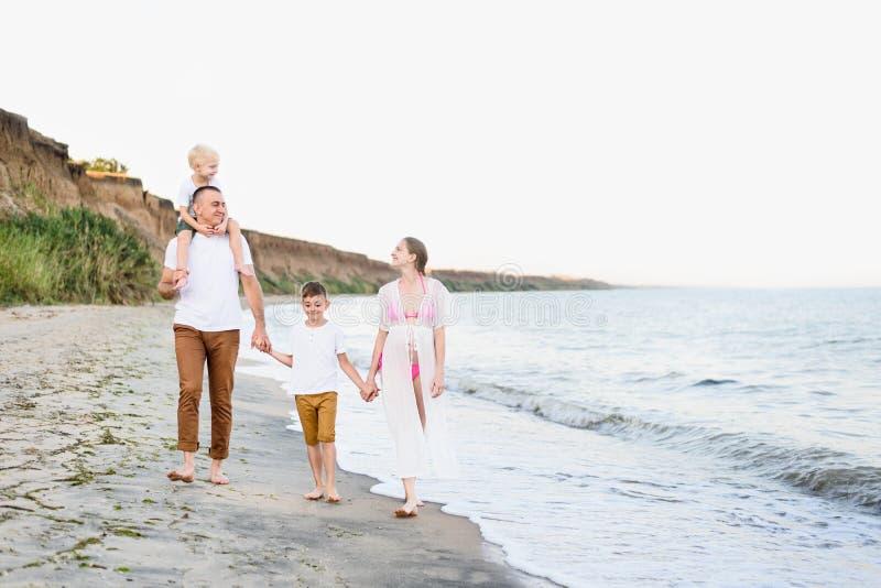 走沿海滨的四口之家 父母和两个儿子 愉快的友好的家庭 库存图片