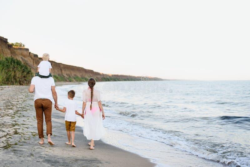 走沿海滨的四口之家 父母和两个儿子 r 免版税库存照片