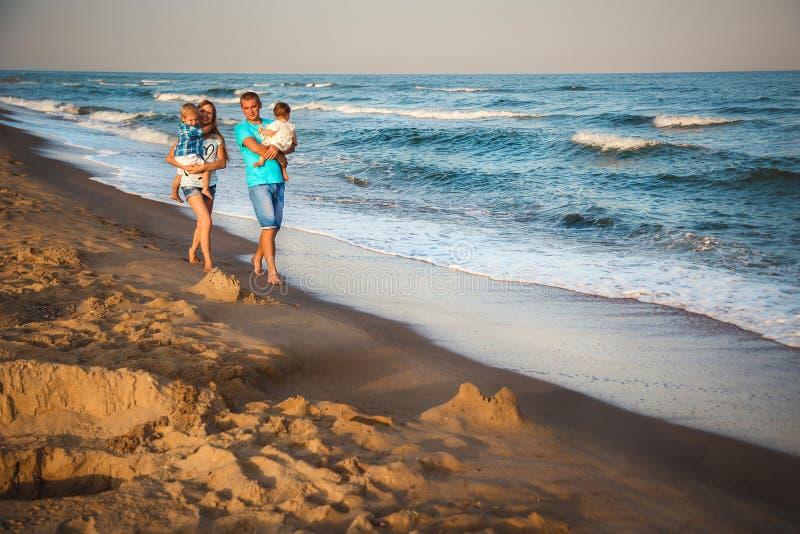 走沿海滩的父亲、母亲和孩子,在海洋附近,愉快的生活方式家庭观念 免版税库存照片