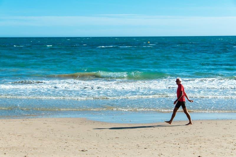 走沿海滩的老人 免版税库存图片