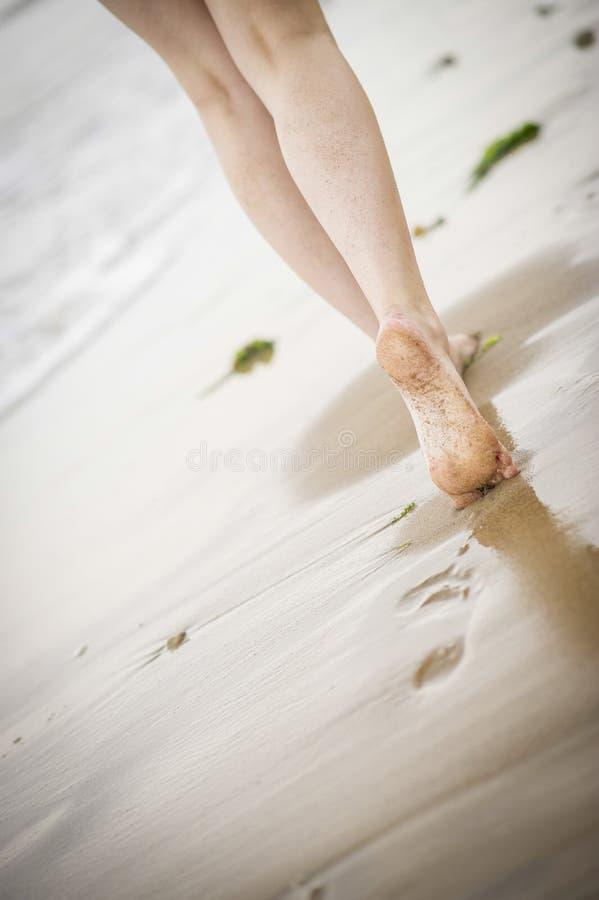 走沿海滩的妇女的腿 免版税库存照片