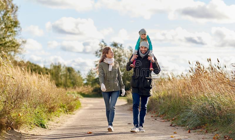 走沿秋天路的幸福家庭 免版税库存照片