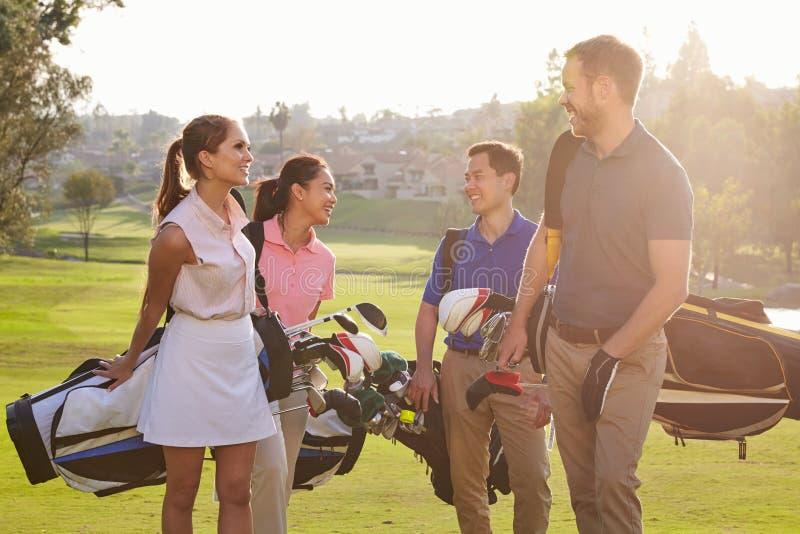走沿航路运载的高尔夫球袋的小组高尔夫球运动员 免版税库存图片