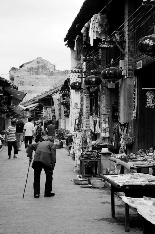 走沿街道的一个老妇人 免版税库存照片