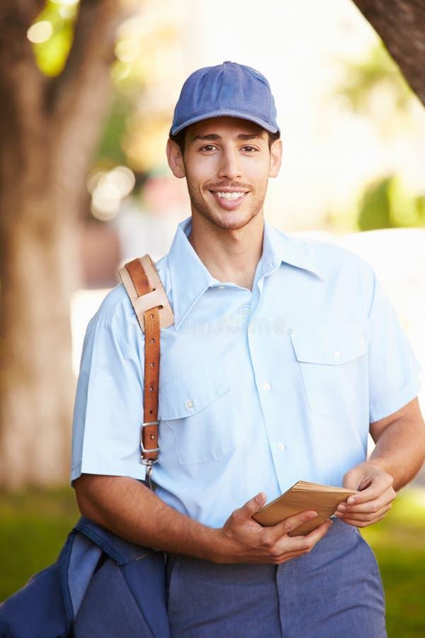 走沿街道的邮递员提供信件 免版税库存图片