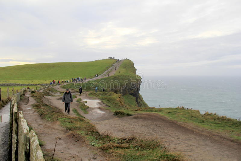 走沿道路的人们在大风天在Moher,爱尔兰, 2014年10月峭壁  库存照片