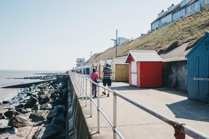 走由五颜六色的海滩小屋的两人由海在谢林汉姆,诺福克,英国 免版税图库摄影
