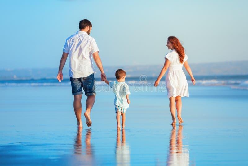 走由日落海滩的家庭 免版税库存照片
