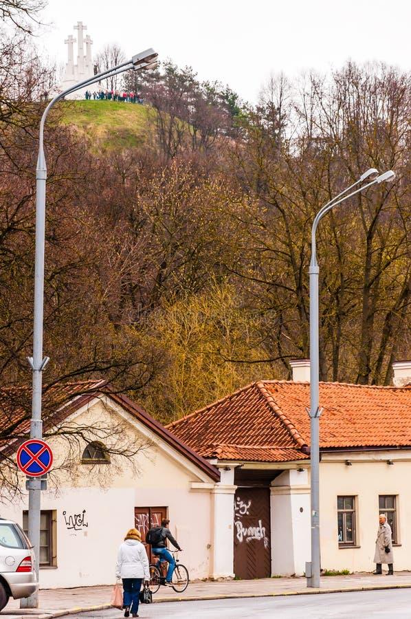 走由有三个十字架纪念碑的Radvilaites街道的人们在背景的小山在维尔纽斯,立陶宛奥尔德敦  图库摄影