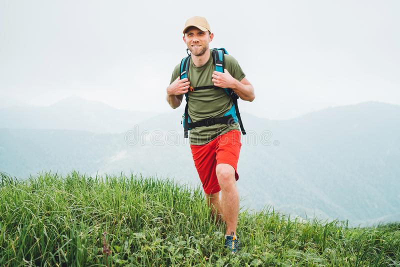 走由有背包的有雾的多云天气山脉道路的疲乏的微笑的徒步旅行者人 活跃体育挑运健康 免版税图库摄影