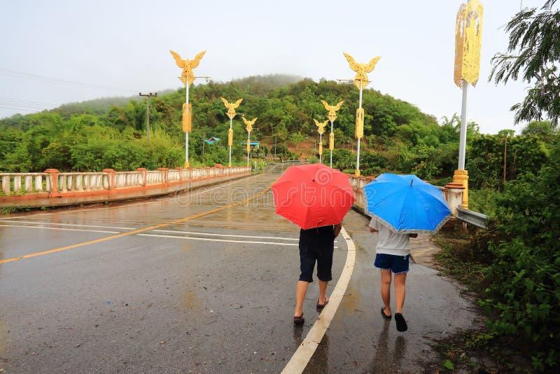 走的人们拿着雨伞 免版税库存照片